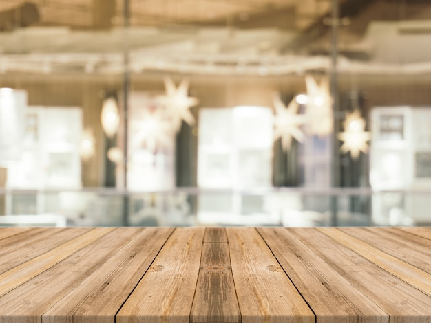 Wooden board empty table top blur in coffee shop background.