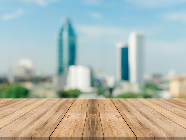 木製のボード空のテーブルトップぼやけた背景。見通しの茶色の木製のテーブルの上にぼかし街の建物のビューの背景 - モンタージュ製品の表示やデザインのキーの視覚的レイアウトのためにモックアップすることができます。