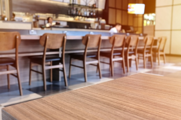 Wooden board empty table top in front of blurred cafe or restaurant