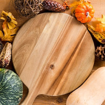 Wooden board framed by autumn harvest