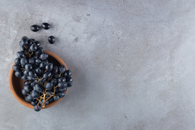 Wooden board of fresh black grapes and glass of wine on stone table.
