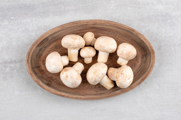 A wooden board of fresh white mushrooms on stone surface.