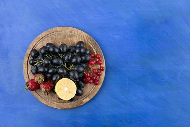 Una tavola di legno piena di frutti di bosco e limone a fette