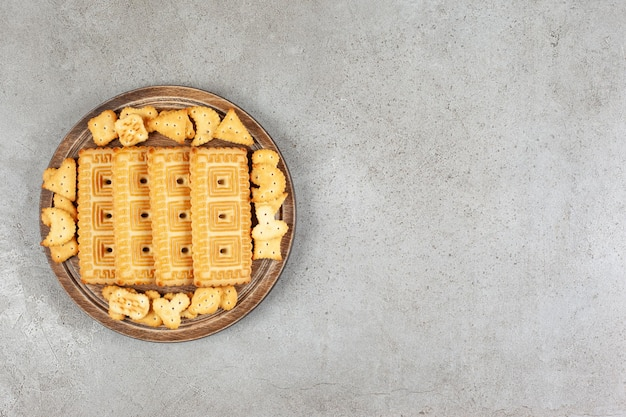A wooden board full of biscuits on marble background.