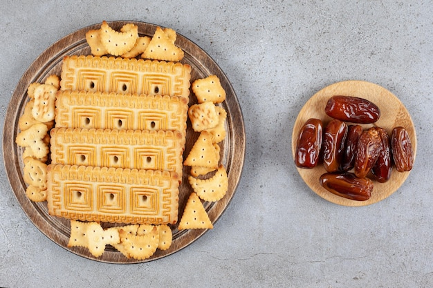 A wooden board full of biscuits on marble surface
