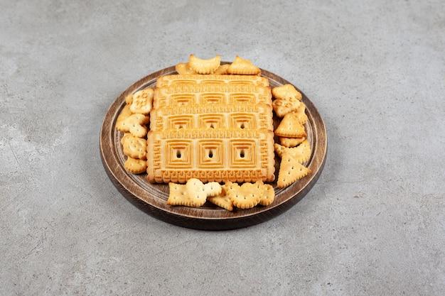 Una tavola di legno piena di biscotti sulla superficie in marmo