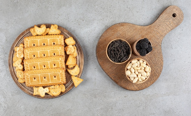 A wooden board full of biscuits on marble surface.