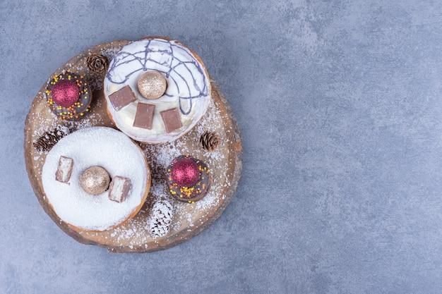Una tavola di legno piena di torte con zucchero in polvere