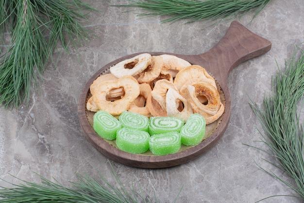 Una tavola di legno piena di mele secche e marmellata di zucchero su fondo di marmo.