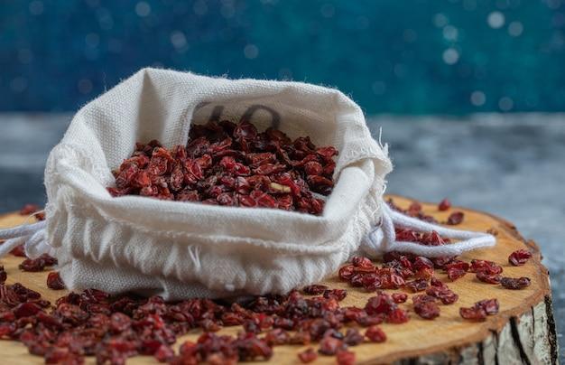 Una tavola di legno piena di mirtilli rossi secchi.