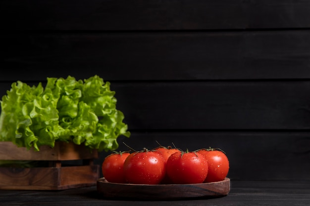 A wooden board full of fresh red juicy tomatoes with lettuce salad. high quality photo