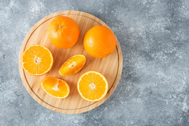 A wooden board full of juicy slices of orange fruit on stone table .