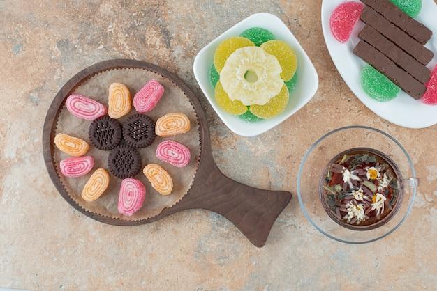 Una tavola di legno piena di marmellata e biscotti