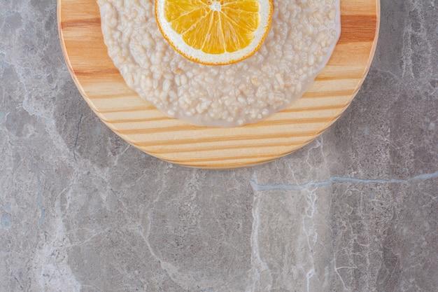 A wooden board full of oatmeal porridge with a slice of orange .