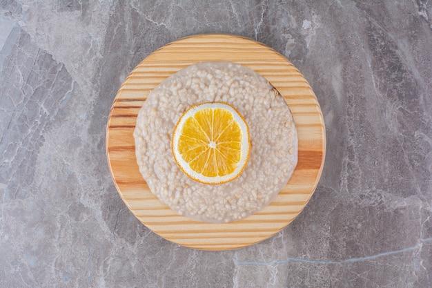 A wooden board full of oatmeal porridge with a slice of orange