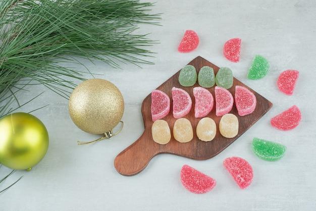 白い背景の上の砂糖マーマレードとクリスマスのお祝いのボールでいっぱいの木の板。高品質の写真