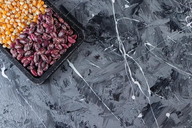 Tavola di legno piena di semi e fagioli crudi su fondo di marmo.
