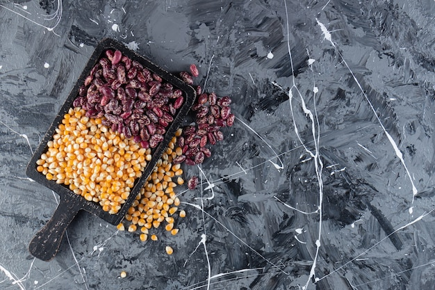 Wooden board full of raw corns and beans on marble background.