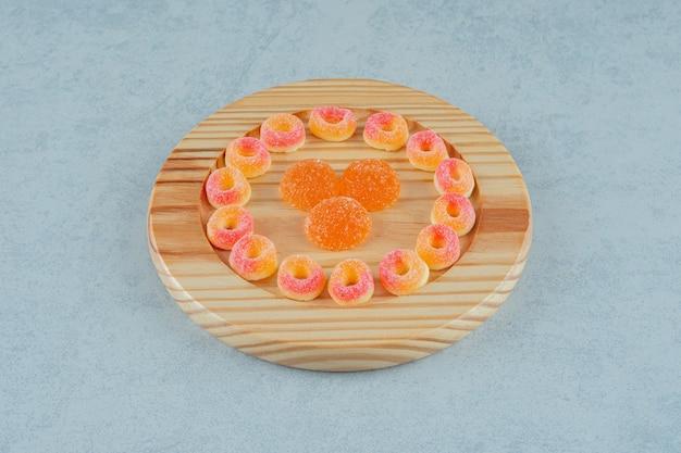 Una tavola di legno piena di caramelle rotonde di gelatina di arancia a forma di anelli e caramelle di gelatina di arancia con zucchero