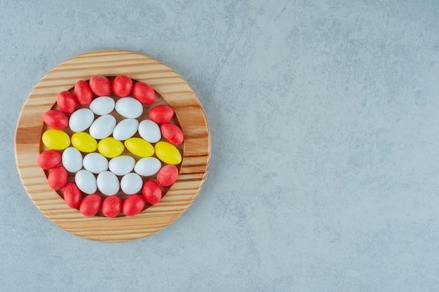Una tavola di legno piena di caramelle colorate dolci rotonde su superficie bianca white