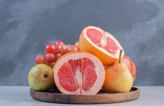 Tagliere di legno pieno di frutta di stagione e pompelmo tagliato a metà.