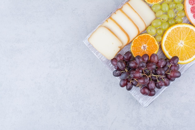 A wooden board full of sliced fruits and bread . high quality photo