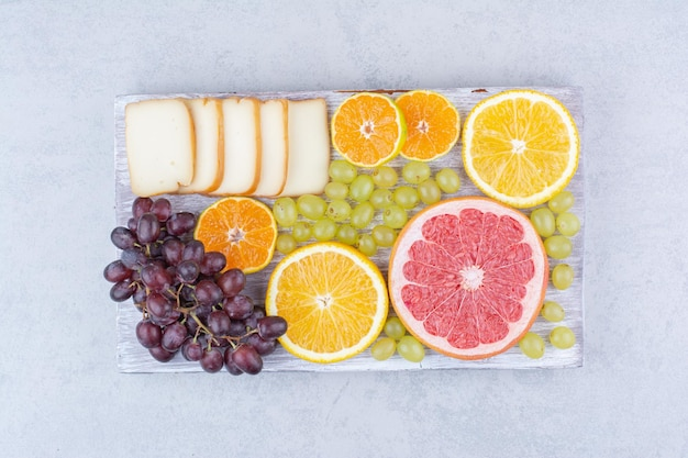 A wooden board full of sliced fruits and bread