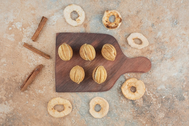 A wooden board full of sweet cookies and cinnamon sticks