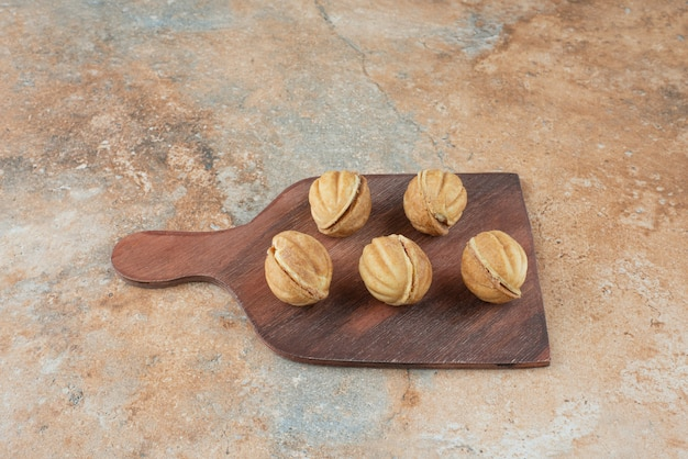 A wooden board full of sweet cookies on marble background