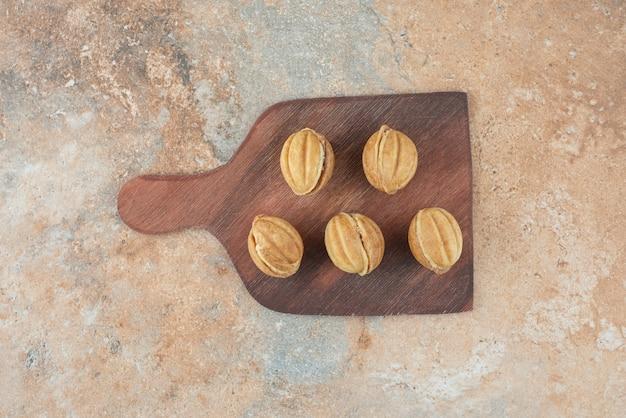 Una tavola di legno piena di biscotti dolci su sfondo di marmo