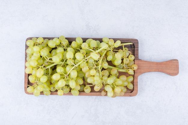 Una tavola di legno piena di uva dolce su bianco