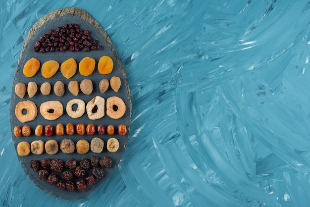 Wooden board full of tasty dried fruits on blue surface.