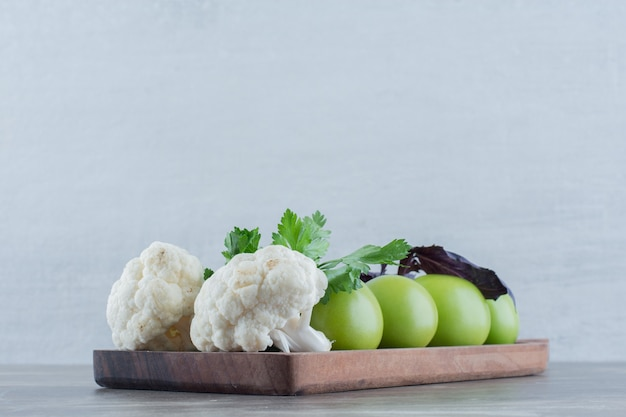 Wooden board of green tomatoes and cauliflower pieces topped with amaranth and parsley leaves on marble.