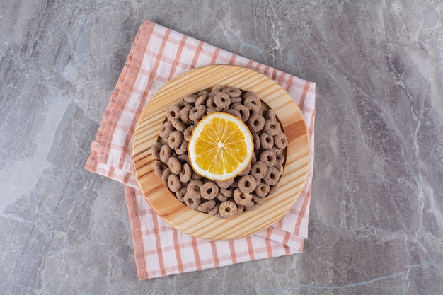 A wooden board of healthy chocolate cereal rings with a slice of orange fruit.
