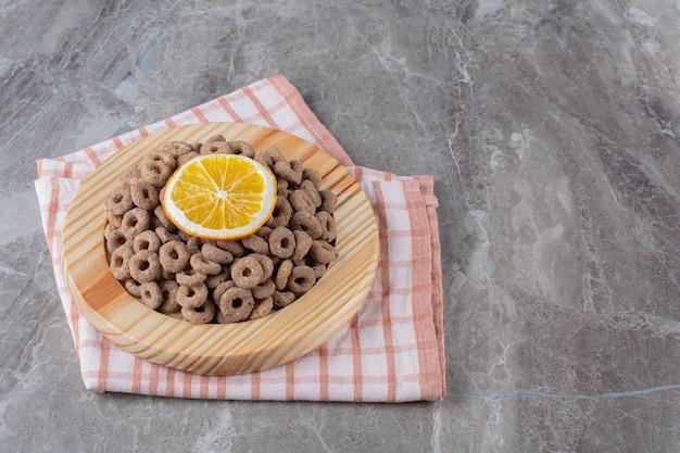 Una tavola di legno di anelli di cereali al cioccolato sani con una fetta di frutta arancione.