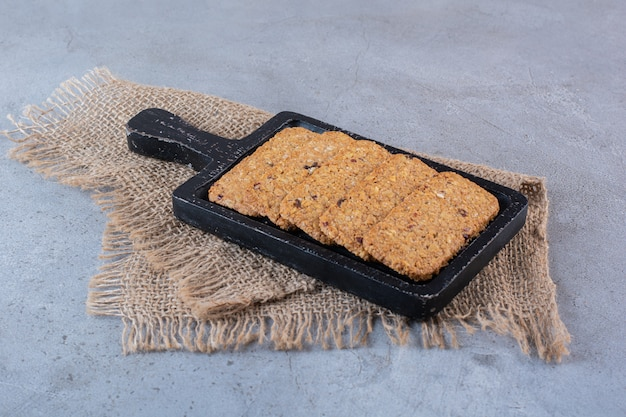 A wooden board of healthy granola bars on a stone surface