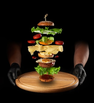 Wooden board and layers of a large cheeseburger floating in the air