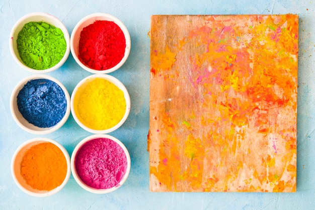 Wooden board mess with holi color powder on painted background