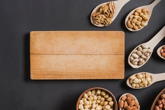 Wooden board near spoons and bowls with nuts