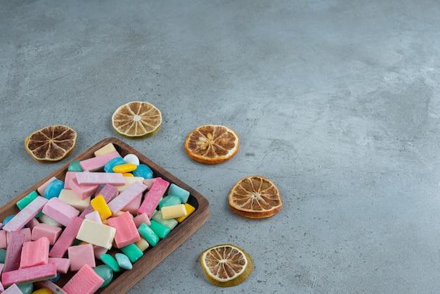다채로운 풍선 껌과 돌에 레몬 조각의 나무 보드.