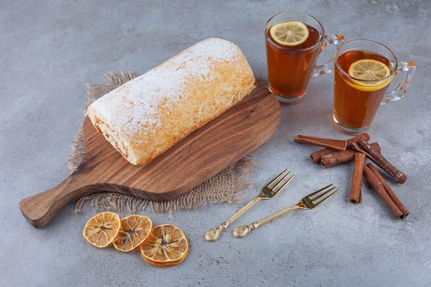 Деревянная доска вкусного бисквитного торта с чашками чая на мраморной поверхности.