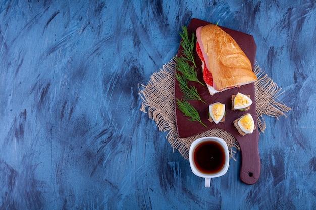 뜨거운 차 한잔과 함께 만든 신선한 샌드위치의 나무 보드.
