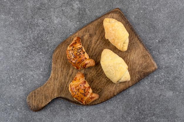 石のテーブルに新鮮なクッキーを混ぜた木の板。
