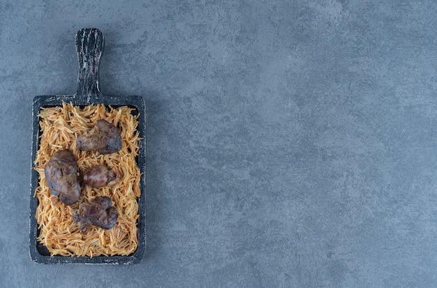 Деревянная доска макарон с сухим мясом на каменной поверхности.