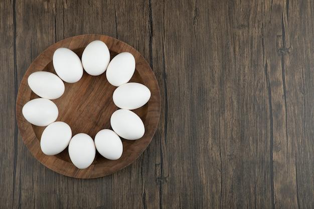 木の表面に生の有機卵の木板。