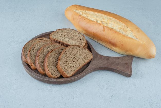 石の表面にライ麦パンとロールパンの木板