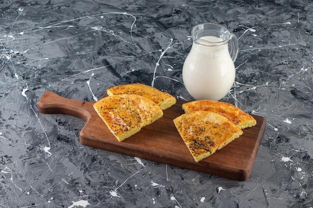 大理石の背景にスライスした焼きたてのペストリーとミルクのガラスの木製ボード。