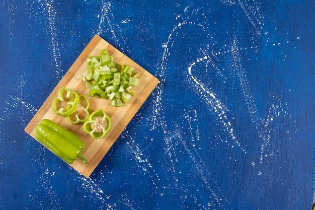 Деревянная доска нарезанного зеленого болгарского перца на мраморном столе.