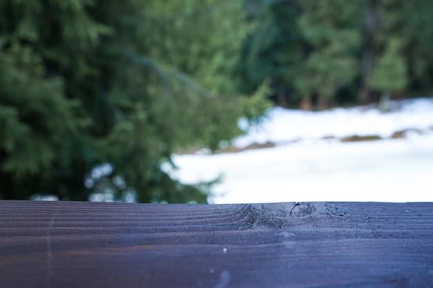 Деревянная доска на фоне леса со снегом