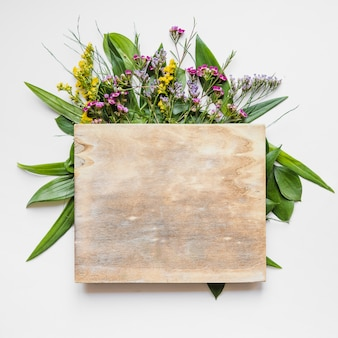Wooden board on leaves and flowers